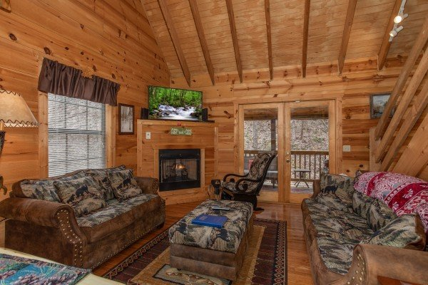 Living room with fireplace, TV, and two sofas at My Smoky Mountain Hideaway, a 3 bedroom cabin rental located in Pigeon Forge