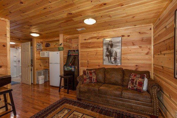 Pull out sofa, arcade game, and kitchenette on the lower level at My Smoky Mountain Hideaway, a 3 bedroom cabin rental located in Pigeon Forge