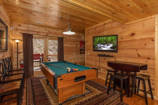 Pool table and TV on the lower level at My Smoky Mountain Hideaway, a 3 bedroom cabin rental located in Pigeon Forge