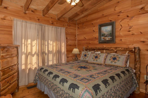 King bed and log dresser in a bedroom at My Smoky Mountain Hideaway, a 3 bedroom cabin rental located in Pigeon Forge