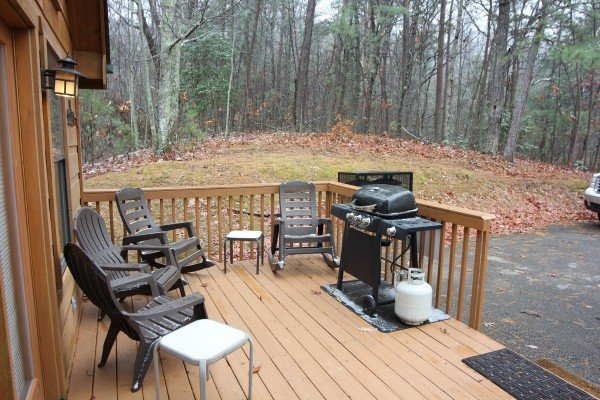 Rockers, chairs, and a propane grill on the deck at Gnarled Oak, a 2-bedroom cabin rental located in Gatlinburg