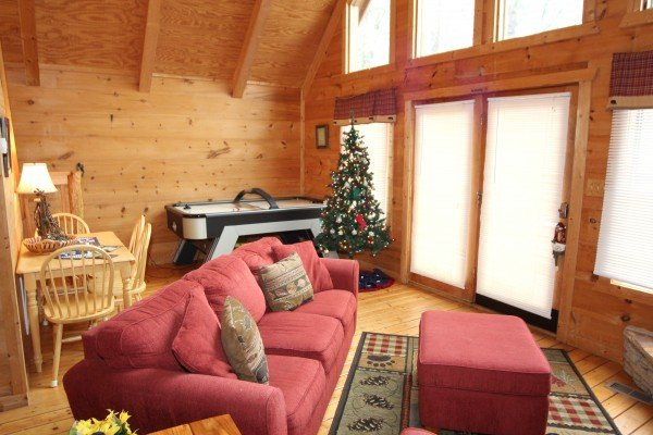 Dining space for four, an air hockey table, and deck access in the living room at Gnarled Oak, a 2-bedroom cabin rental located in Gatlinburg