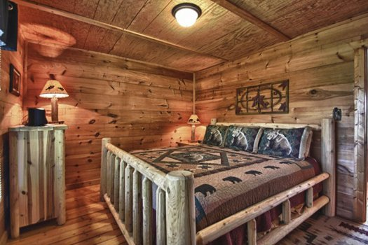 Bedroom with a king-sized log bed at Gnarled Oak, a 2-bedroom cabin rental located in Gatlinburg