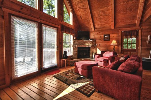 Living room with vaulted ceiling and floor-to-ceiling windows at Gnarled Oak, a 2-bedroom cabin rental located in Gatlinburg