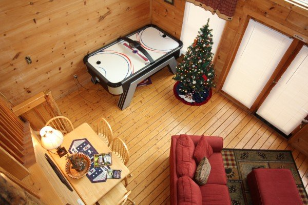 Looking down on the air hockey table and dining table at Gnarled Oak, a 2-bedroom cabin rental located in Gatlinburg