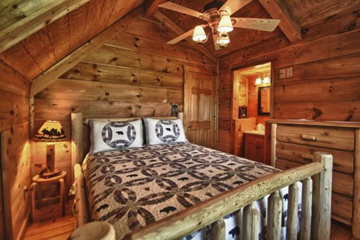 Queen-sized log bed in the loft at Gnarled Oak, a 2-bedroom cabin rental located in Gatlinburg