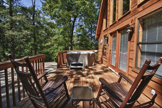 Hot tub and two rocking chairs on the deck at Gnarled Oak, a 2-bedroom cabin rental located in Gatlinburg