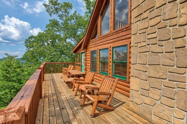 Adirondack chairs, picnic table, and rocking chairs on the deck at Cabin in the Clouds, a 3-bedroom cabin rental located in Pigeon Forge