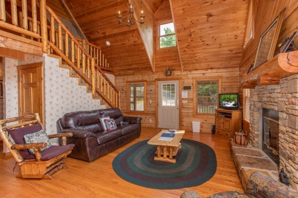 Living room with a leather couch, log glider, fireplace, and television at Cabin in the Clouds, a 3-bedroom cabin rental located in Pigeon Forge