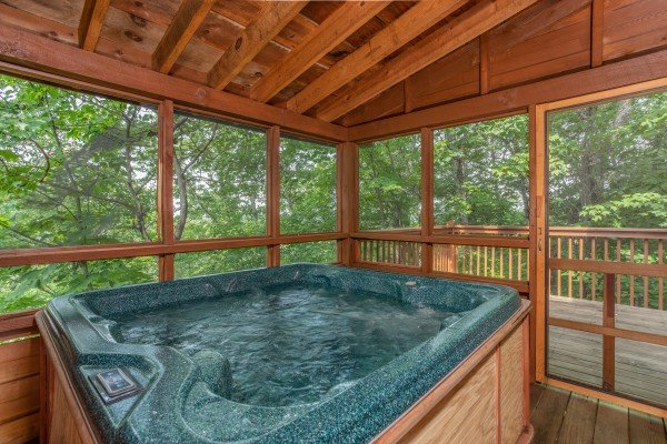 Hot tub on a covered, screened-in porch at Cabin in the Clouds, a 3-bedroom cabin rental located in Pigeon Forge