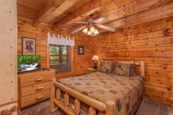Log bed, dresser, and a television in a bedroom at Cabin in the Clouds, a 3-bedroom cabin rental located in Pigeon Forge