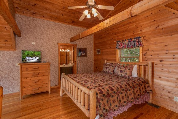 King-sized log bed with a dresser television in a vaulted ceiling bedroom at Cabin in the Clouds, a 3-bedroom cabin rental located in Pigeon Forge