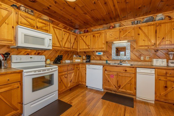 Kitchen with white appliances at Hatcher Mountain Retreat a 2 bedroom cabin rental located in Pigeon Forge