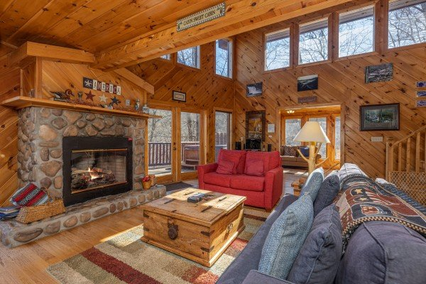 Living room with a fireplace and TV at Hatcher Mountain Retreat a 2 bedroom cabin rental located in Pigeon Forge