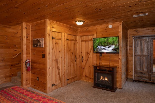 Electric fireplace and TV in the bedroom at Knotty Nest, a 1 bedroom cabin rental located in Pigeon Forge