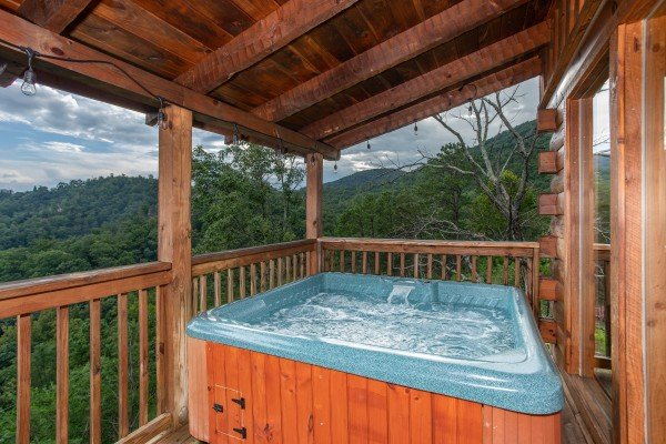 Hot tub on a covered deck surrounded by mountain views at Knotty Nest, a 1 bedroom cabin rental located in Pigeon Forge