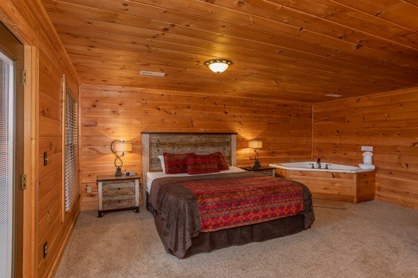 Bedroom with a king bed and corner jacuzzi tub at Knotty Nest, a 1 bedroom cabin rental located in Pigeon Forge