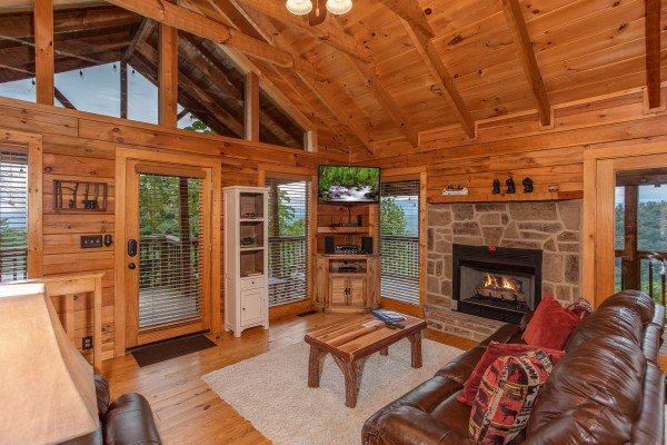 Living room with vaulted ceiling and large windows at Knotty Nest, a 1 bedroom cabin rental located in Pigeon Forge