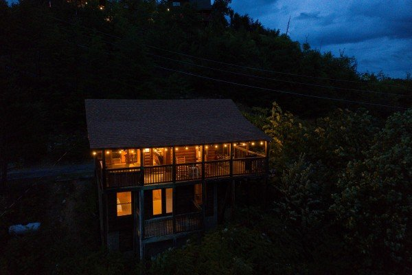 Looking back at the cabin lit at night at Knotty Nest, a 1 bedroom cabin rental located in Pigeon Forge
