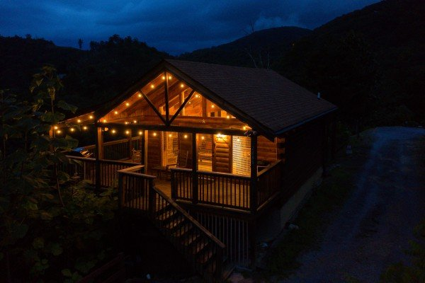 The cabin lit at night at Knotty Nest, a 1 bedroom cabin rental located in Pigeon Forge
