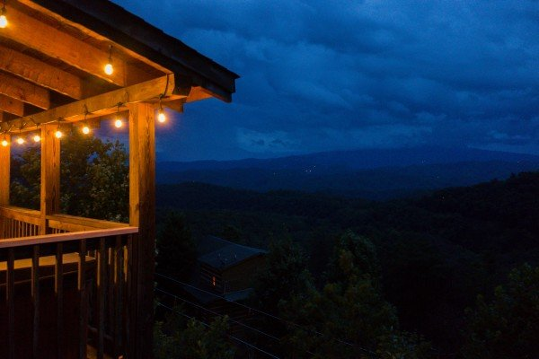 Lighted porch and the night sky at Knotty Nest, a 1 bedroom cabin rental located in Pigeon Forge