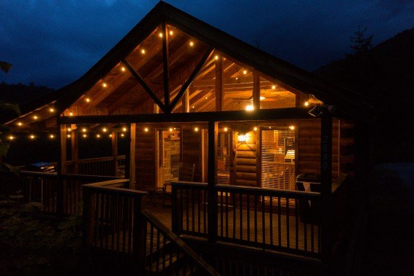 A cabin lit up at night called Knotty Nest, a 1 bedroom cabin rental located in Pigeon Forge
