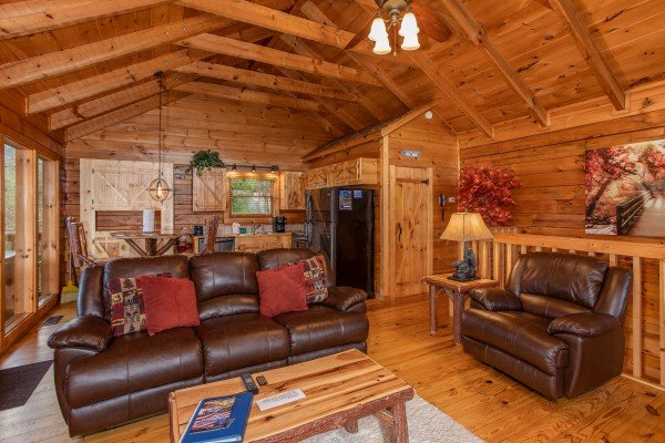 Open concept main floor with living room, dining space, and kitchen at Knotty Nest, a 1 bedroom cabin rental located in Pigeon Forge