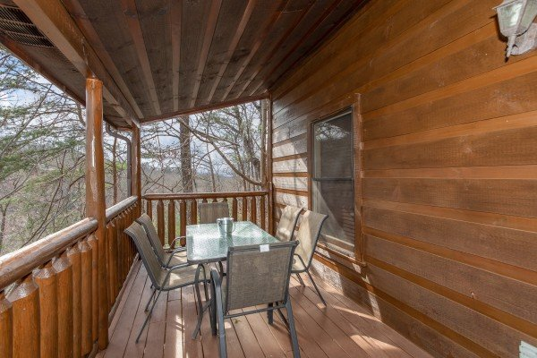 Dining space for six on a covered deck at Altitude Adjustment, a 1 bedroom cabin rental located in Pigeon Forge