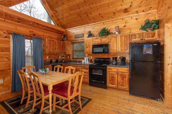 Dining table for six in a kitchen with black appliances at Altitude Adjustment, a 1 bedroom cabin rental located in Pigeon Forge