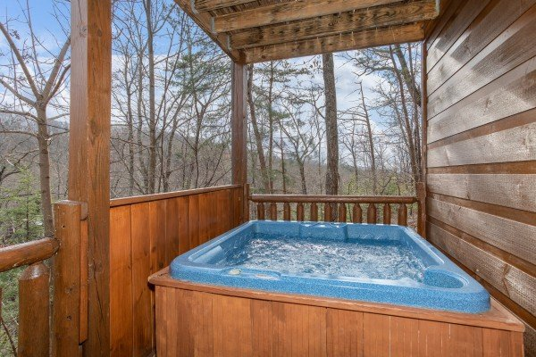 Hot tub on a covered deck at Altitude Adjustment, a 1 bedroom cabin rental located in Pigeon Forge