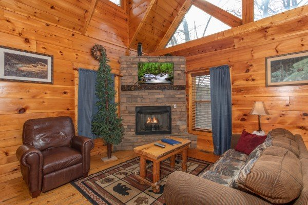 Living room with fireplace, TV, vaulted ceiling, and high windows at Altitude Adjustment, a 1 bedroom cabin rental located in Pigeon Forge