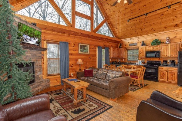 Living room, dining space, and kitchen on the main floor at Altitude Adjustment, a 1 bedroom cabin rental located in Pigeon Forge