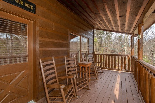 Rocking chairs on a covered deck at Altitude Adjustment, a 1 bedroom cabin rental located in Pigeon Forge