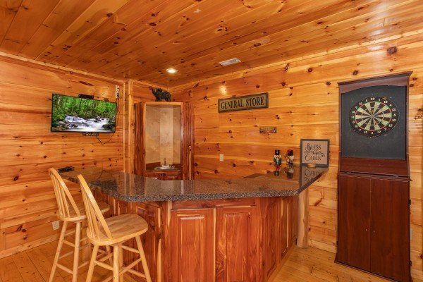 Wet bar with TV and dart board at Altitude Adjustment, a 1 bedroom cabin rental located in Pigeon Forge