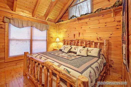 bedroom with king sized log framed bed at fishin' hole a 1 bedroom cabin rental located in gatlinburg