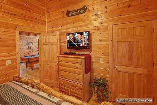 Chest of drawers with tv mounted above in bedroom at Fishin' Hole, a 1-bedroom cabin rental located in Gatlinburg