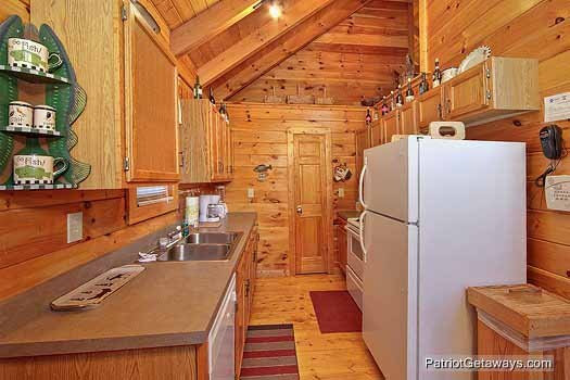Kitchen with white appliances at Fishin' Hole, a 1-bedroom cabin rental located in Gatlinburg