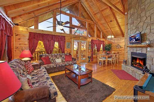 living room with stone fireplace and two sofa beds at fishin' hole a 1 bedroom cabin rental located in gatlinburg
