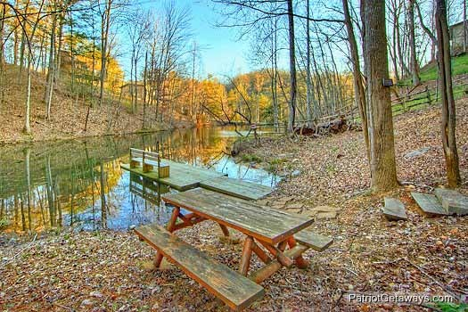 Picnic table by the dock on the river at Fishin' Hole, a 1-bedroom cabin rental located in Gatlinburg