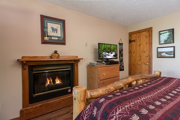 Bedroom with a fireplace, dresser, and TV at Ridge View, a 1 bedroom cabin rental located in Pigeon Forge