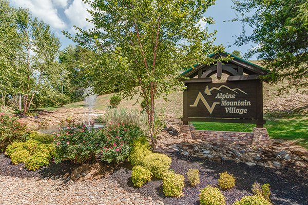 Alpine Mountain Village resort sign at Bear Essence, a 2-bedroom cabin rental located in Pigeon Forge