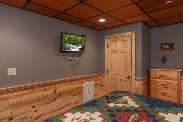 Wall mounted television in the lower bedroom at Bear Essence, a 2-bedroom cabin rental located in Pigeon Forge