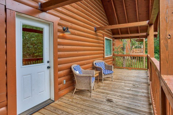 Front porch with two wicker chairs at Bear Essence, a 2-bedroom cabin rental located in Pigeon Forge