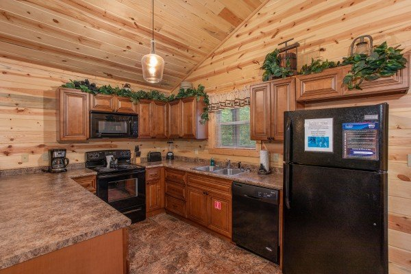Kitchen with black appliances at Bear Essence, a 2-bedroom cabin rental located in Pigeon Forge