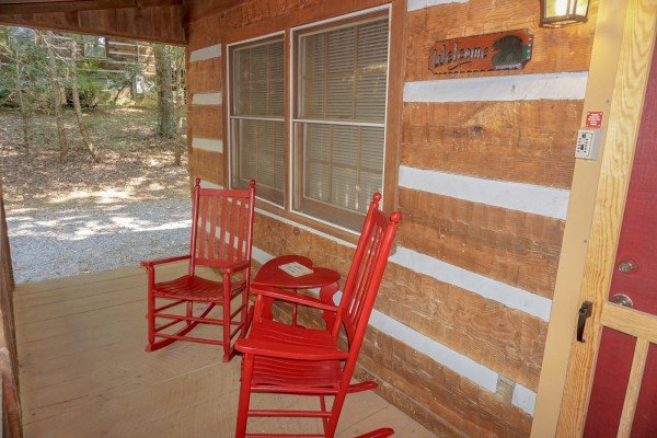 Red rocking chairs on the covered front porch at Little Bear, a 1 bedroom cabin rental located in Pigeon Forge