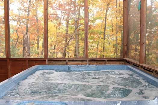 Hot tub on a screened in deck at Little Bear, a 1 bedroom cabin rental located in Pigeon Forge
