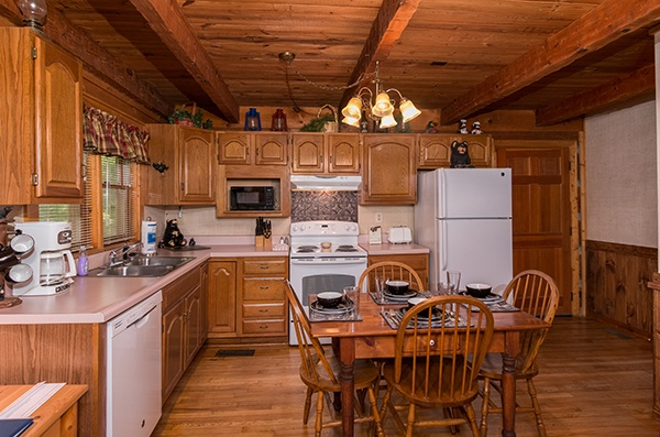 Kitchen with white appliances and a dining table for four at Little Bear, a 1 bedroom cabin rental located in Pigeon Forge