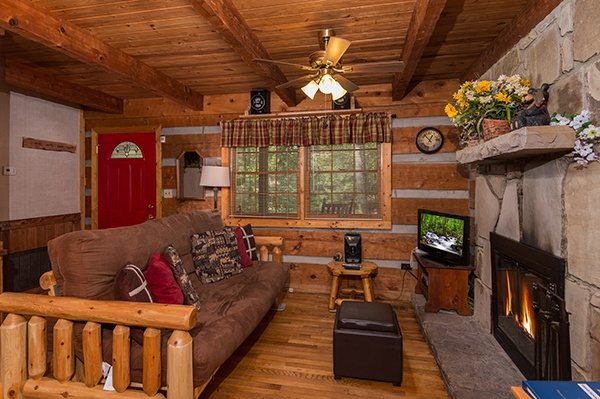 Living room with a futon, TV, and fireplace at Little Bear, a 1 bedroom cabin rental located in Pigeon Forge