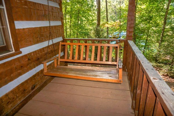 A closer look at the porch swing on the covered deck surrounded by woods at Little Bear, a 1 bedroom cabin rental located in Pigeon Forge
