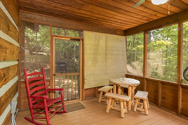 Dining table for four and a rocking chair on the screened in deck at Little Bear, a 1 bedroom cabin rental located in Pigeon Forge